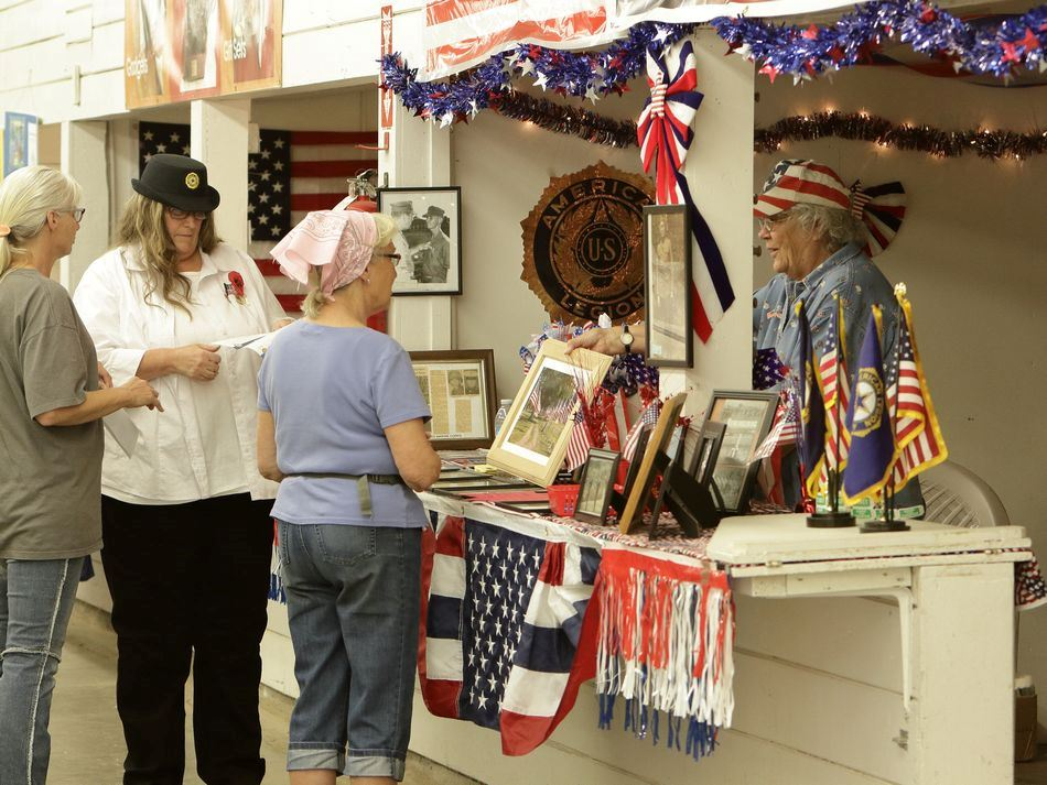 A woman shows a picture to onlookers at a booth at the Klickitat County Fair.
